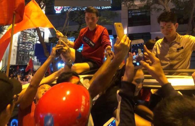 Ca sĩ nổi tiếng ngồi vắt vẻo trên nóc ôtô xem người dân hồ hởi mừng chiến thắng của đội tuyển U23 Việt Nam trong trận bán kết gặp Qatar.